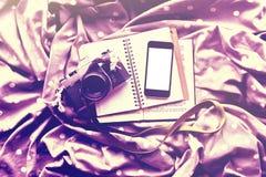 Tom mobiltelefon, kamera för gammal stil, tom dagbok och en bok Royaltyfri Bild