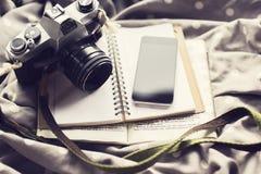Tom mobiltelefon, kamera för gammal stil, tom dagbok och en bok Fotografering för Bildbyråer