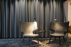Tom modern grå stol två med ljus och en tabell mellan Gardiner på en bakgrund royaltyfri bild