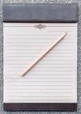 Tom notepad med blyertspennan på den bruna skrivplattan Royaltyfri Foto