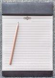 Tom notepad med blyertspennan på den bruna skrivplattan Arkivfoton