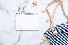 Tom notepad, randig sommarpåse, snäckskal på marmorbakgrund Kvinnors skrivbord av handelsresanden, skönhetblogger, digital nomad, royaltyfri bild