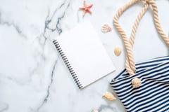 Tom notepad, randig sommarpåse, snäckskal på marmorbakgrund Kvinnors skrivbord av handelsresanden, skönhetblogger, digital nomad, royaltyfri foto