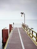 Tom pir i hamn Stålspisgallerbräde Den svarta kormoran sitter på lampan Arkivbilder