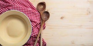 Tom platta, köksgeråd och röd bordduk på trätabellen, bästa sikt, kopieringsutrymme royaltyfri foto