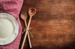 Tom platta, köksgeråd och röd bordduk på trätabellen, bästa sikt, kopieringsutrymme fotografering för bildbyråer