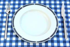 Tom platta, kniv och gaffel på den Chrckered picknickbordduken Royaltyfria Foton