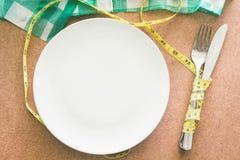Tom platta med den måttbandet, kniven och gaffeln på trätabellen royaltyfria foton
