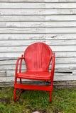 Tom röd metallstol bredvid övergiven gammal byggnad Arkivfoto