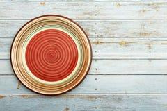 Tom röd platta för keramisk maträtt med den spiral modellen på trävit blå bakgrund B?sta sikt med kopieringsutrymme arkivbild