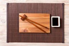 Tom rektangulär träplatta för sushi med sås och pinnar på trätabellen, bästa sikt arkivfoto