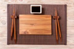 Tom rektangulär träplatta för sushi med sås och pinnar på trätabellen, bästa sikt royaltyfria foton