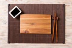 Tom rektangulär träplatta för sushi med sås och pinnar på trätabellen, bästa sikt arkivbilder