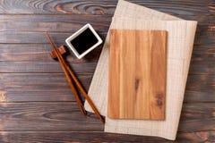Tom rektangulär träplatta för sushi med sås och pinnar på trätabellen, bästa sikt arkivfoton