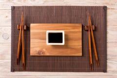 Tom rektangulär träplatta med pinnar för sushi och soya på träbakgrund B?sta sikt med kopieringsutrymme arkivfoton