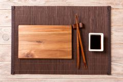 Tom rektangulär träplatta med pinnar för sushi och soya på träbakgrund B?sta sikt med kopieringsutrymme arkivfoto