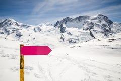 Tom riktningsteckenstolpe med landskap för vintersnöberg Arkivbild