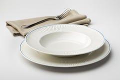 Tom rund vit platta och bunke med servetten och gaffeln Arkivbild