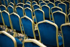 tom salongbio ett stort antal blåa sammetstolar i rad royaltyfri foto