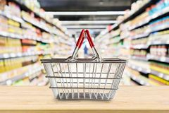 Tom shoppingkorg på den wood tabellen över livsmedelsbutik arkivbild