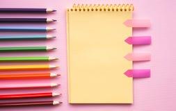 Tom sida av det vertikala spiral skissa blocket med färgpennor på rosa bakgrund arkivbilder
