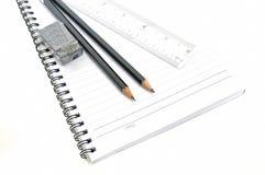 Tom sida med blyertspennor, radergummit och linjalen Arkivfoto