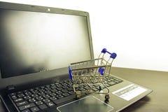 Tom skärm för datoranteckningsbok med shoppingvagnen på den wood tabellen royaltyfria foton