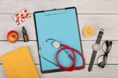 tom skrivplatta, preventivpillerar, frukter, bok, stetoskop, glasögon och klocka på träbakgrund royaltyfri bild