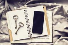 Tom smartphone med tangenter för gammal stil på den tomma dagboken och boken Arkivbild