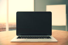 Tom svart bärbar datorskärm på trätabellen på tom kontorsbackgr royaltyfria foton