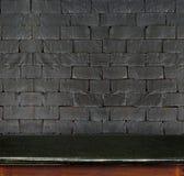 Tom svart för marmortabell och svart tegelstenvägg för vit i backgroun arkivfoto