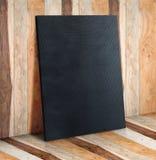 Tom svart kanfas på träplankaväggen och golv, förlöjligar upp till dis Arkivbilder