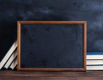 Tom svart kritateckningsram och bunt av böcker arkivfoto
