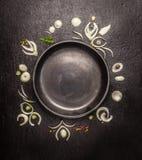Tom svart platta med ramen av lökskivor och kryddor på mörk stenbakgrund, bästa sikt arkivbilder