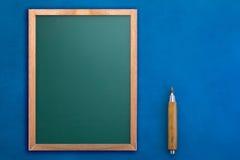 Tom svart tavla med blyertspennan på blå bakgrund jpg Arkivbilder