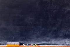 Tom svart tavla med kulöra chalks Arkivfoto