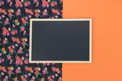Tom svart tavla på orange bakgrund med kopieringsutrymme Arkivbilder