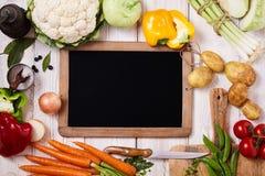 Tom svart tavla som omges av nya grönsaker royaltyfri foto