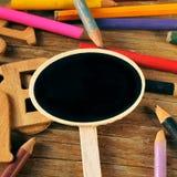 Tom svart tavlaetikett och färgade blyertspennor på lantliga trälodisar royaltyfria bilder