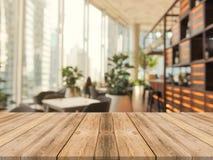 Tom tabellöverkant för träbräde på av suddig bakgrund Brun wood tabell för perspektiv över suddighet i coffee shopbakgrund arkivfoton