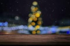 Tom tabell för träbräde framme av den suddiga julgranen och girlander av ljusbakgrundsaftonen arkivfoto