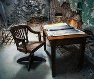 Tom tabell och stol i det gamla fängelset fotografering för bildbyråer