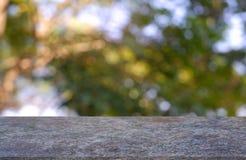 Tom tabell som är främst av abstrakt suddig gräsplan av trädgård- och naturljusbakgrund För montageproduktskärm royaltyfri foto