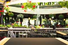 Tom tabell som är främst av en suddig bakgrund Ett ljust gatakafé med blommor, växter och en springbrunn - kan vara van vid skärm royaltyfria bilder
