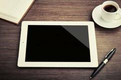 Tom tablet och ett kaffe på skrivbordet Arkivbilder