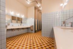 Tom toalett med handfatet och avskilda toalettkabiner i ett modernt vandrarhem Royaltyfria Foton