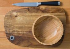 Tom träbunke och kniv på träskärbräda på trälodisar royaltyfri fotografi