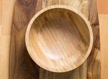 Tom träbunke på träskärbräda på träbakgrund arkivbild
