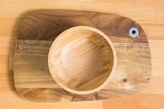 Tom träbunke på träskärbräda på träbakgrund royaltyfri bild