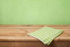 Tom trädäcktabell med den kontrollerade bordduken över grön väggbakgrund Arkivfoton